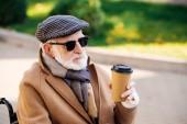 Fotografie Close-up Portrait des senior behinderte Menschen im Rollstuhl hält Pappbecher Kaffee auf Straße