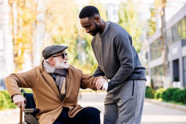 young african american cuidador helping senior disabled man to get up from wheelchair on street