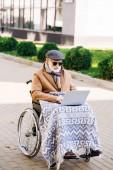 Senior Mann im Rollstuhl mit Plaid arbeiten mit Laptop auf Straße gesperrt