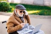 schöner älterer behinderter Mann im Rollstuhl mit Laptop und Kopfhörer auf der Straße