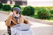 Senior behinderter Mann im Rollstuhl mit Laptop und Kopfhörer auf der Straße