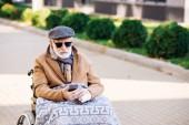 Senior zakázán muž na invalidním vozíku pomocí smartphone na ulici