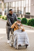 Fotografie senior disabled man in wheelchair listening musing with smartphone and earphones with african american cuidador on street