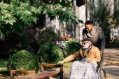 Fotografie šťastní senioři zakázán člověka do invalidního vozíku a africký Američan cuidador tráví čas spolu na ulici