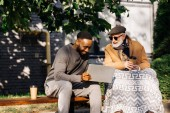 senior disabled man in wheelchair and african american man using laptop together on street