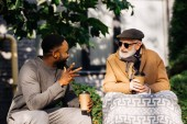 senior disabled man in wheelchair and african american man drinking coffee from paper cups and chatting on street
