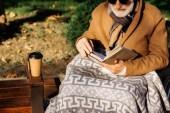 oříznuté shot senior postižený člověk na vozíku čtení knihy na ulici