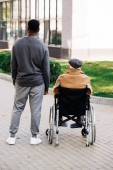 Fotografie rear view of senior disabled man in wheelchair and young african american cuidador spending time together on street