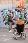 Fotografie back view of senior disabled man in wheelchair looking at african american man playing basketball on street