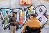 zadní pohled na senior postižený člověk na vozíku při pohledu na afroamerické muže hrát basketbal na ulici