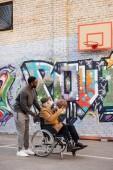 Senior fogyatékkal élő ember tolószékben boldog afrikai amerikai férfi kosárlabda együtt játszottak a street