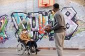 Fotografie šťastní senioři zakázán muž v invalidní vozík a afroamerické muže hrát basketbal společně na ulici