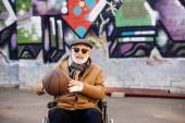Senior fogyatékkal élő ember tolószékben látszó-nél fényképezőgép street kosárlabda labda