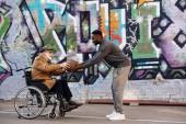 boční pohled na zakázané důstojník v invalidní vozík a afroamerické muže hrát basketbal společně na ulici