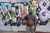 Fotografie africké americké aristokratickým krasavcem basketbalový míč při pohledu na fotoaparát na ulici před barevné graffiti