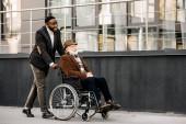 Fotografie glücklich Senior behinderte Menschen im Rollstuhl und African American Cuidador Straße fahren