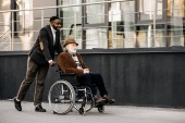 smiling senior disabled man in wheelchair and african american man riding by street