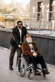 happy senior disabled man in wheelchair and african american man riding by street