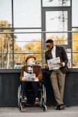 Fotografie senior disabled man in wheelchair and african american man reading newspapers together on street
