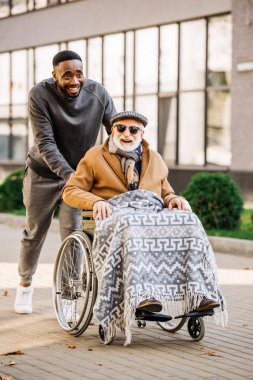 happy senior disabled man in wheelchair with plaid and african american man riding by street