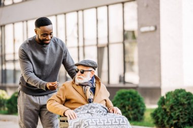 happy african american man giving joint to senior disabled man in wheelchair wjhile they spending time together on street