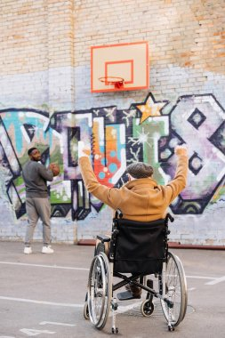 back view of celebrating senior disabled man in wheelchair looking at african american man playing basketball on street