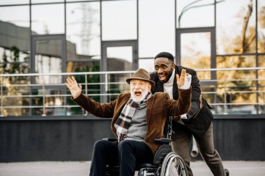 happy senior disabled man in wheelchair and african american man having fun while riding by street
