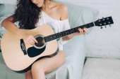 partial view of curly girl playing on acoustic guitar in bedroom at home