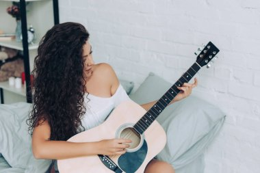 smiling curly girl playing on acoustic guitar in bedroom at home
