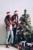 Fotografie pár v santa klobouky, zdobí vánoční stromeček doma