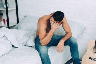high angle view of shirtless man in jeans sitting on bed at home