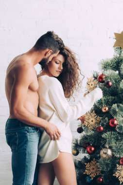 shirtless muscular man embracing attractive girlfriend near christmas tree at home