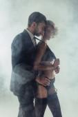 Fotografie Man hugging blonde wonderful woman in lingerie while she pulling him by cravat on grey smoke background