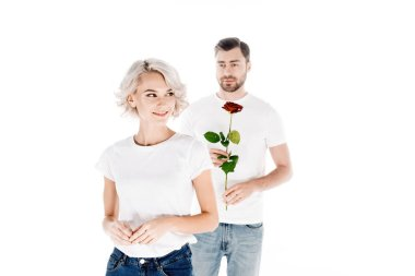 Beautiful smiling woman looking away while man holding flower isolated on white