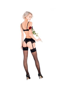 Seductive blonde woman in black lingerie holding beautiful red rose isolated on white