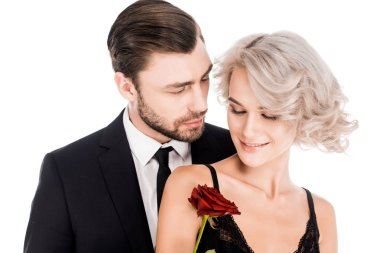 Fantastic couple standing together while woman holding flower isolated on white