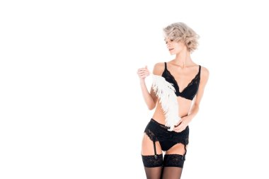 Blonde young tender woman in black lingerie with white feather isolated on white