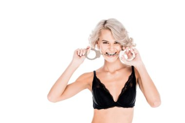 Attractive blonde young adult with handcuffs in mouth isolated on white