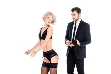 Wonderful woman standing in lingerie and handcuffs while man holding whip isolated on white