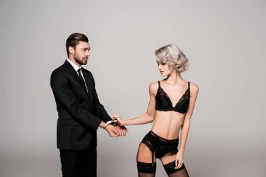 Seductive woman holding hands of handsome man in handcuffs in lingerie isolated on grey