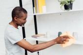 Fotografie africká americká zralý muž čištění prachu z regálu