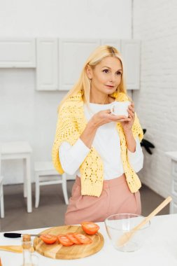 beautiful woman standing with cup of coffee at kitchen