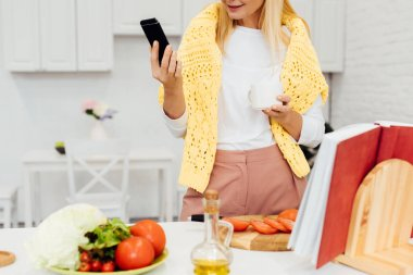cropped view of blonde woman holding smartphone while cooking dinner