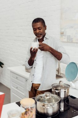 african american mature man holding white cup while standing at kitchen