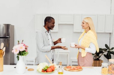 mature blonde woman and african american man drinking coffee together at kitchen