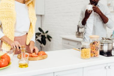 cropped view of mature blonde woman cooking dinner while african american man drinking coffee