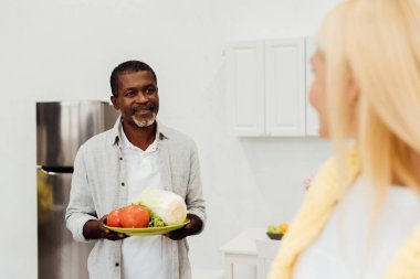 african american man holding vegetables and looking at woman