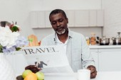 african american man sitting at table and reading travel newspaper at kitchen