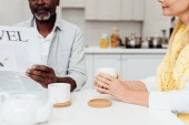 close up of african american man reading newspaper while woman drinking tea