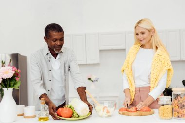 smiling woman slicing tomatoes on chopping board while african american man holding plate with vegetables